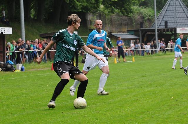 大人のサッカー選手が試合で、ディフェンスを相手にボールをキープしている場面