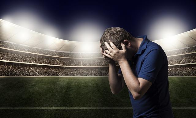 スタジアムを背景に男性が両手で頭を抱えてうつむいている姿