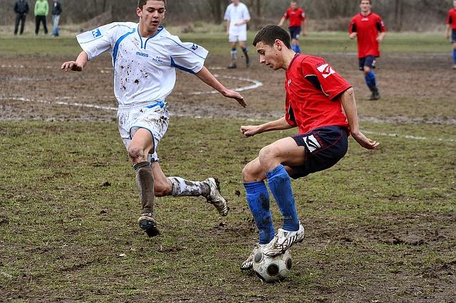 グランドが雨でぬかるんでいる中で、サッカーの試合が行われている様子(オフェンスの選手が左の足裏でボールをコントロールしている)