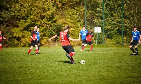 サッカーの試合で、遠くを見ながらボールを蹴ろうとする瞬間の大人の選手