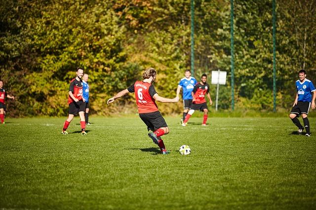 大人のサッカーの試合で、フリーキックを蹴ろうとする瞬間の選手
