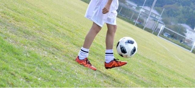 サッカーボールをリフティングしている子共の下半身