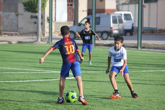 バルセロナのメッシのユニフォームを着た少年が試合の中でドリブルをしている風景