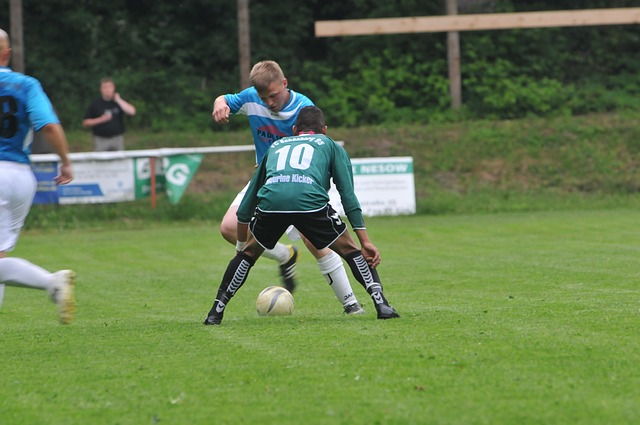 サッカーの試合の1対1で、オフェンスの選手がディフェンスの選手をフェイントで抜こうとしている風景