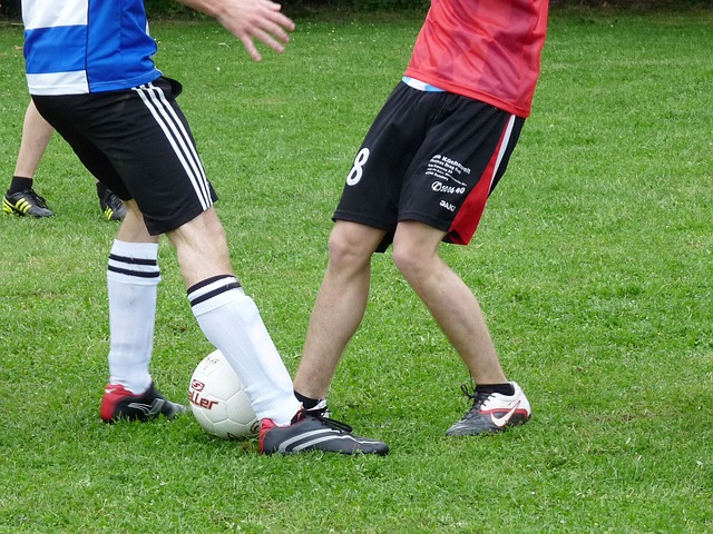 サッカーの1対1でオフェンスとディフェンスの選手がボールを足で奪い合う風景