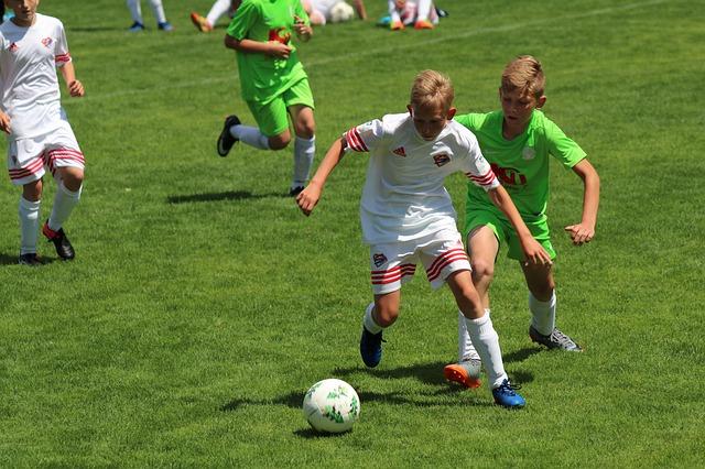 育成年代のサッカーの試合で、相手DFを背にしてボールをキープしている様子