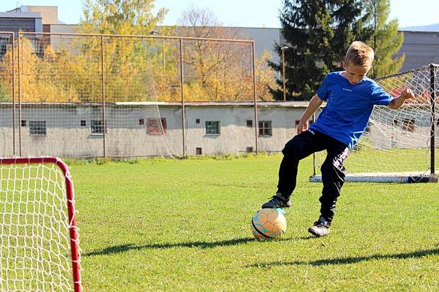 サッカーのミニゴールの近くで、右足をボールに乗せて技術のトレーニングをしている少年