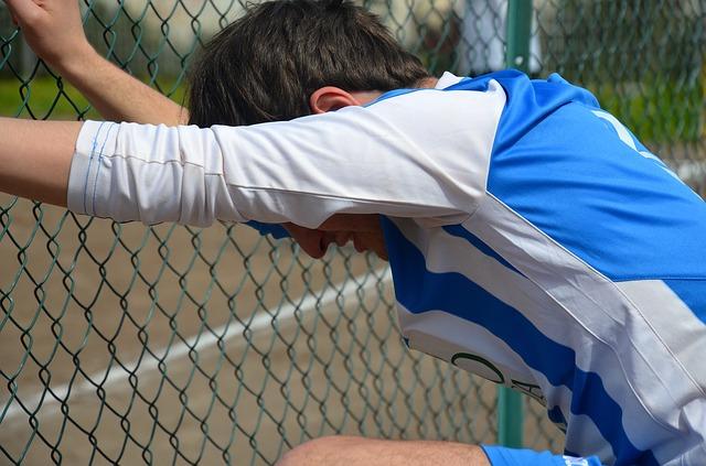 フェンスに両手をかけて顔を下に向けているサッカー選手