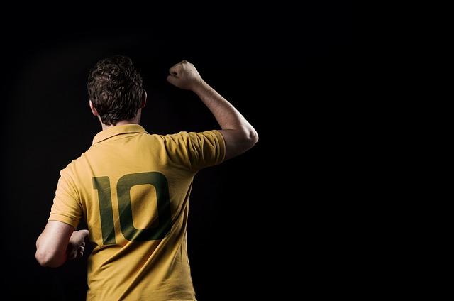 黒い拝啓で右手でガッツポーズをするサッカーのユニフォームを着た男性の姿