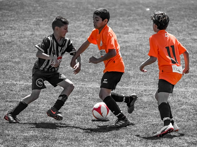 少年サッカーの1対1でオフェンスの選手がディフェンダーの背後にボールを運ぶ場面