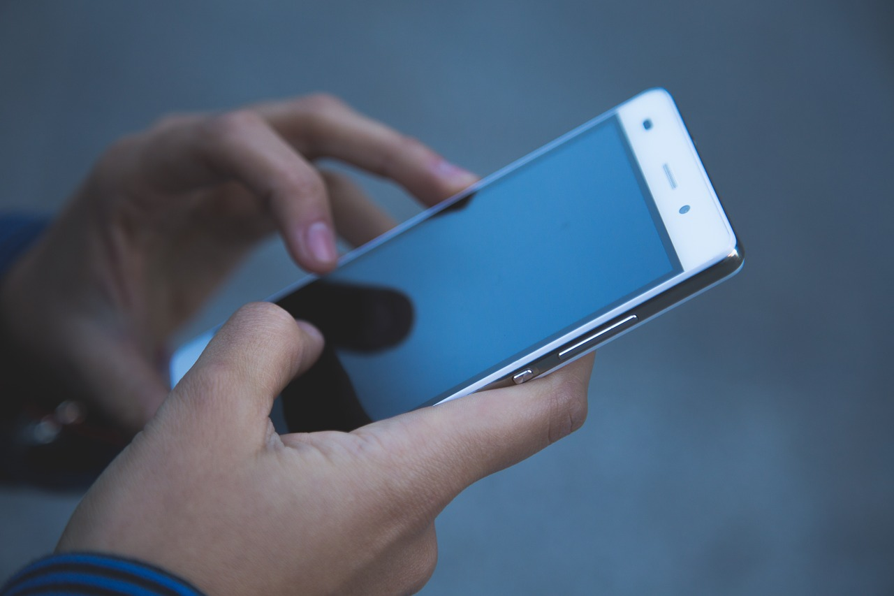 スマートフォンを両手で持ちながら操作をしている手元をズームアップした画像
