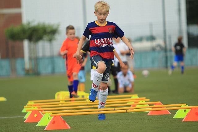 バルセロナのユニフォームを着た少年がミニハードルを使ってトレーニングをしている様子