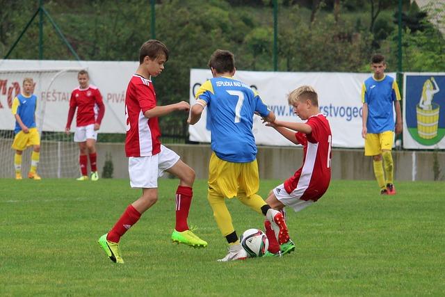 サッカーの試合でディフェンダー2人の選手に挟まれながら、オフェンス選手がドリブルを仕掛けている場面