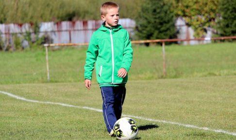 少年が芝の上で足元にサッカーボールを置いている姿