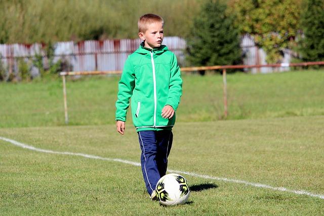少年が芝生の上をサッカーボールと一緒に歩いている様子