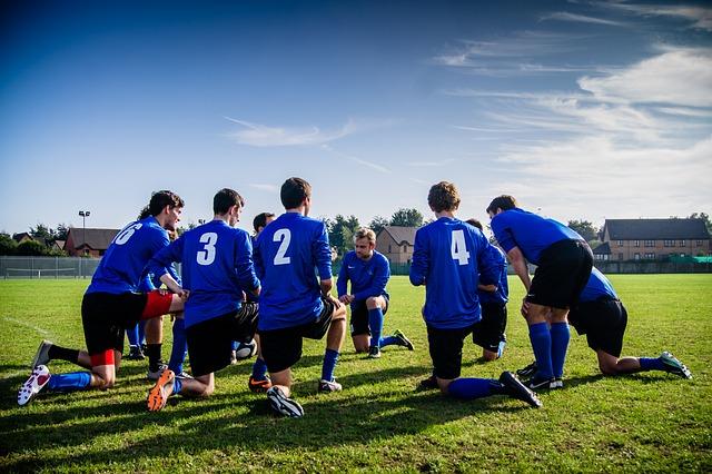 サッカーでチームメイトが輪になって、それぞれ片膝をついて話し合っている様子