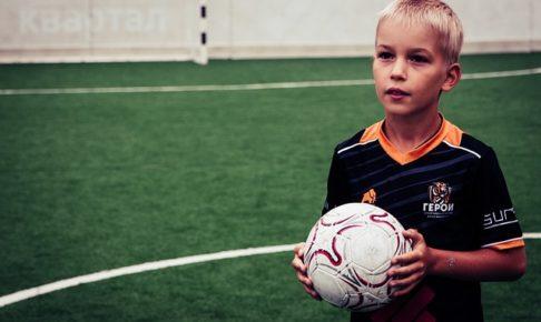 サッカーコートの中で白いサッカーボールを両手で持つ1人の少年