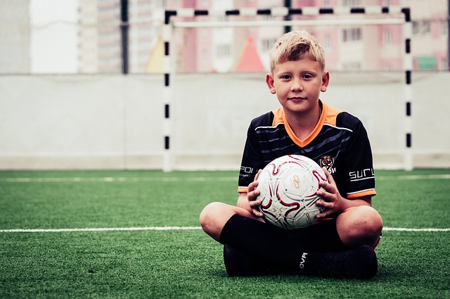 少年がサッカーコートにあぐらをかいて両手でボールを持っている様子