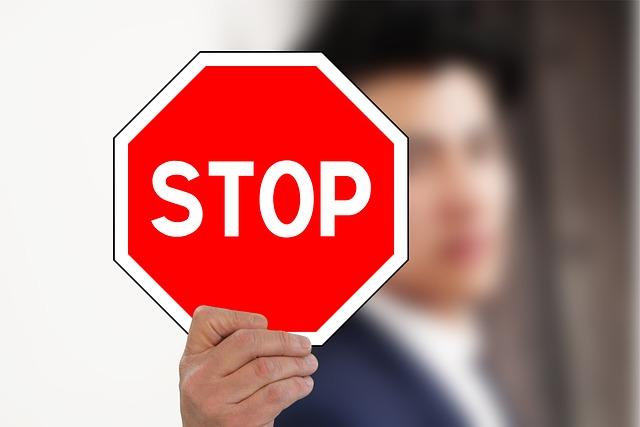 STOPと白く書かれた赤いカードを右手でかざしている画像