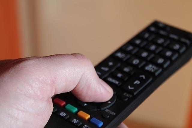 左手の親指でテレビのリモコン操作をズームアップした風景