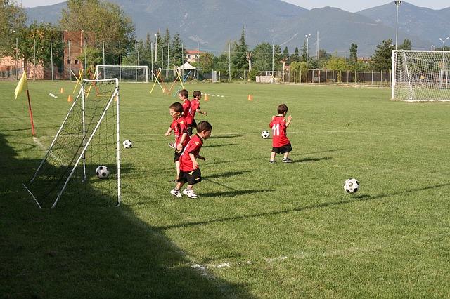 小学生低学年の少年たちが、ミニゴール前でサッカーボールを自由に蹴っている風景