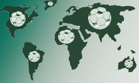 緑系の世界地図と各大陸に白いサッカーボールが描かれたイラスト