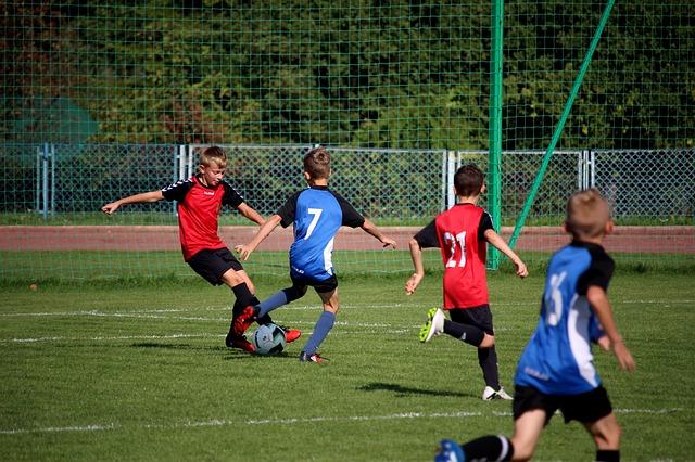 少年サッカーの1対1でオフェンス選手がディフェンス選手をかわそうとしている瞬間