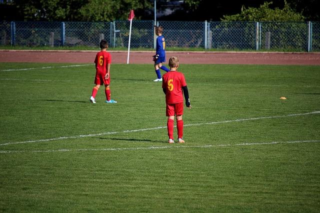 サッカーの試合で背番号5をつけた少年を背後から撮影した風景