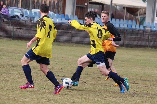 サッカーの試合でオフェンス選手がディフェンス選手をドリブルで抜き去ろうとしている場面