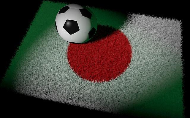 日本の国旗をイメージした芝の上にボールがあるイラスト