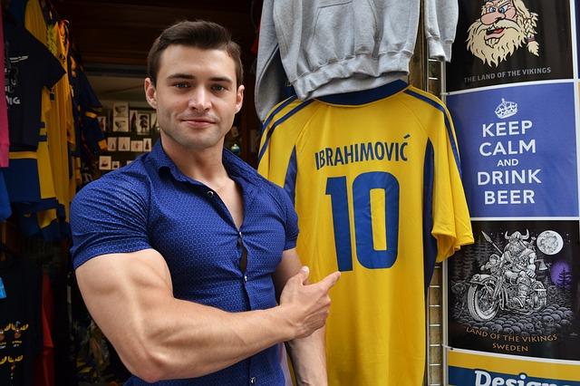 筋肉質な男性が店先に飾ってあっるスウェーデン代表のイブラヒモビッチと書かれたユニフォームを指差してこちらを見ている風景