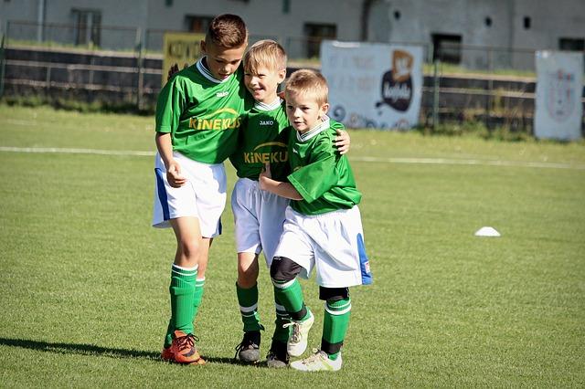 サッカー少年3人が笑顔で肩を抱き合っている姿