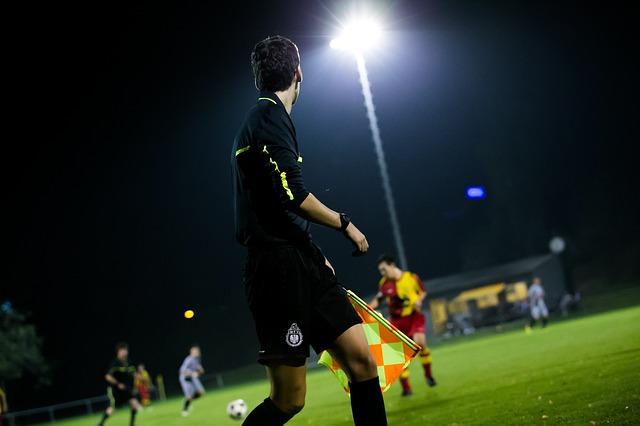 サッカーの試合で黒の上着を着た副審が、試合を見ながらタッチラインを走っている風景