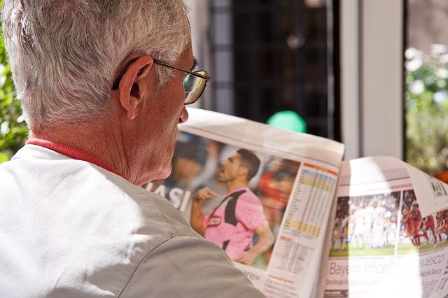外国人の男性が新聞のサッカー記事に目を通している姿を後方から映している様子