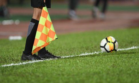サッカーの副審の下半身とサッカーボールを正面から写した風景