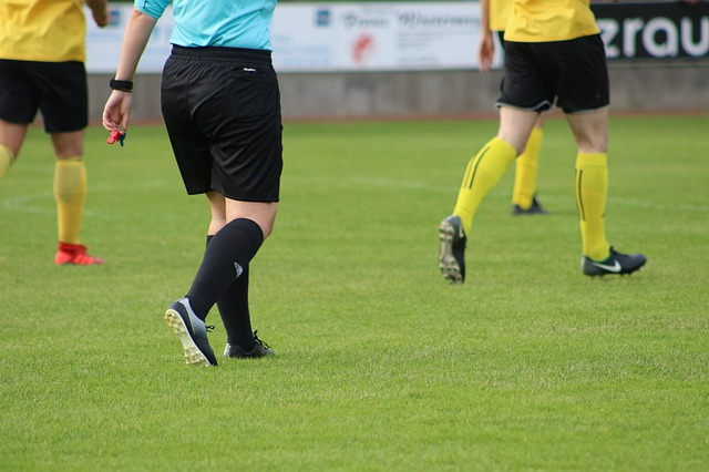 黄色の上着のユニフォームを着たサッカー選手たちと、水色の上着を着た審判の下半身をズームアップした風景