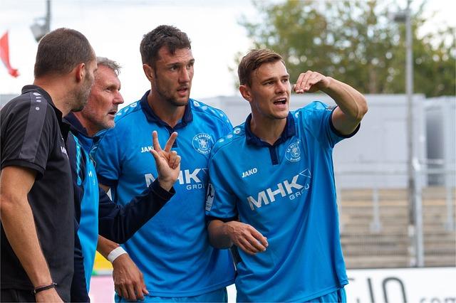 サッカー選手やコーチ・トレーナー4人が身振り手振りで指示を出している風景