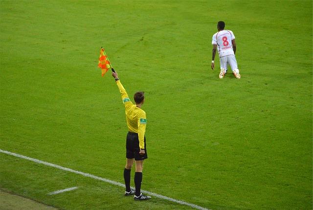 サッカーの試合で黄色の上着を着た副審が左手でフラッグを真上に高く上げて合図をしており、すぐ近くで選手が地面に膝をついている風景