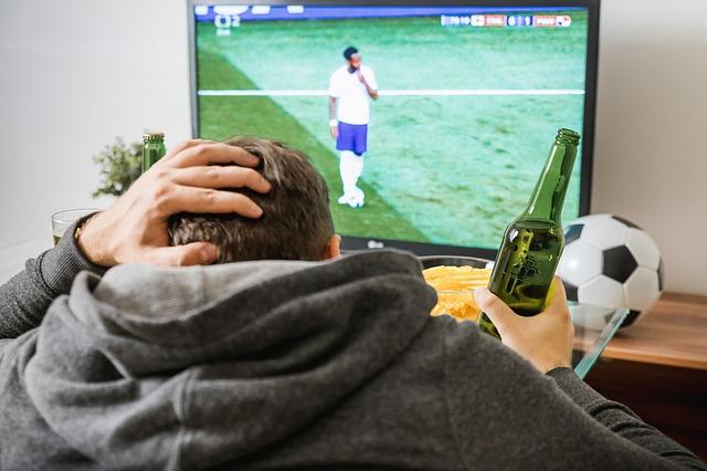 緑のビール瓶を右手に持ち、テレビに映るサッカーの試合観戦をしながら、左手で後頭部を押さえて嘆いている風景