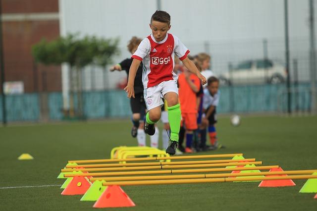 サッカー少年がミニハードルを使ってトレーニングをしている風景