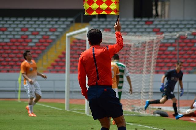 サッカーの試合で、オレンジ色の上着を着た副審がフラッグを真上に上げて合図をしている風景