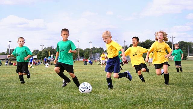 ジュニア年代の子供たちがサッカーボールを追いかけている場面
