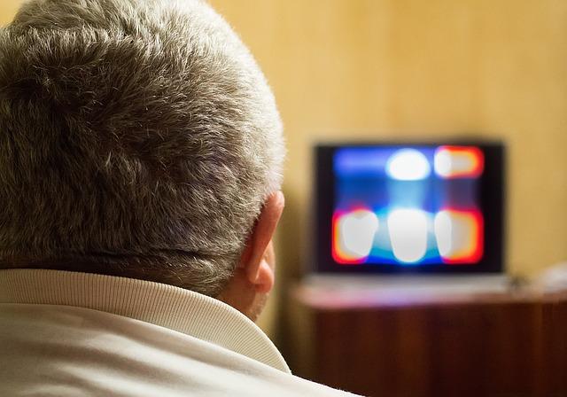 白髪の男性がテレビを視聴している姿を後方から映した様子