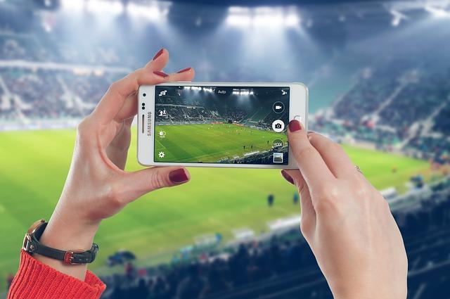 サッカーの試合を観客席からスマートフォンで撮影している風景