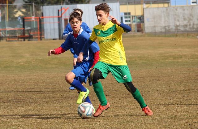 少年サッカーの試合でオフェンスの選手がドリブルをし、それをディフェンスが後方から追いかけている風景
