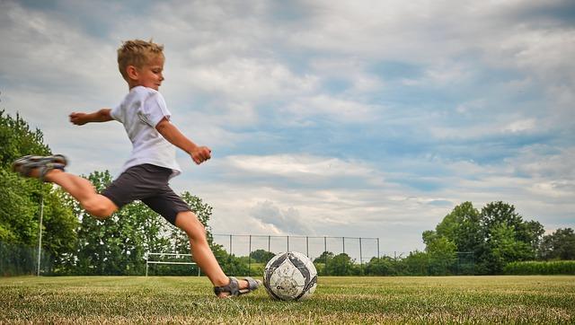 芝生の上で私服の男の子が小さなサッカーボールを右足で蹴ろうとしている風景