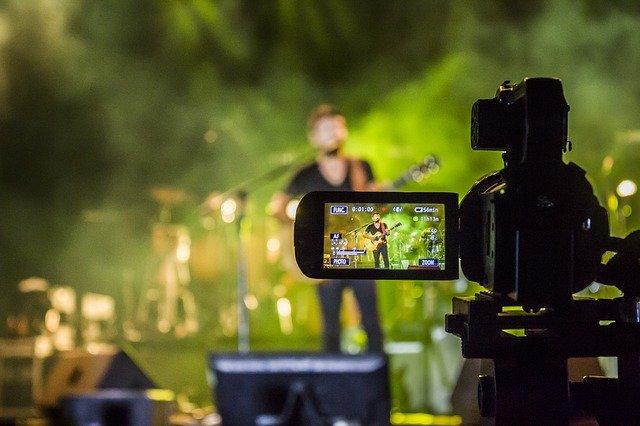 ライブ会場でギターを弾いている歌手をカメラ越しに撮影している風景