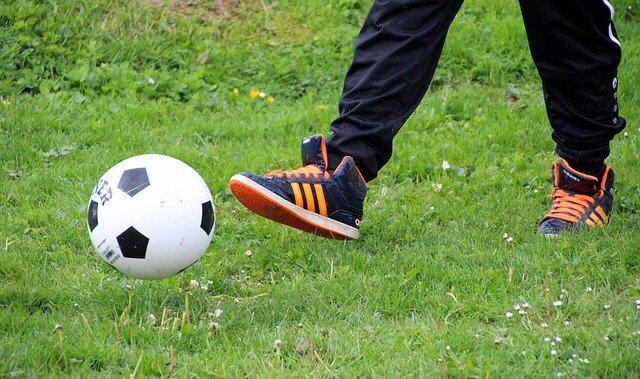 芝の上で小さなサッカーボールを足で蹴っている子供の下半身をズームアップした風景