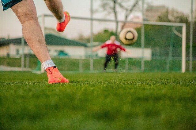 ゴールキーパーがいるサッカーのゴール(目標)にシュートをしている風景