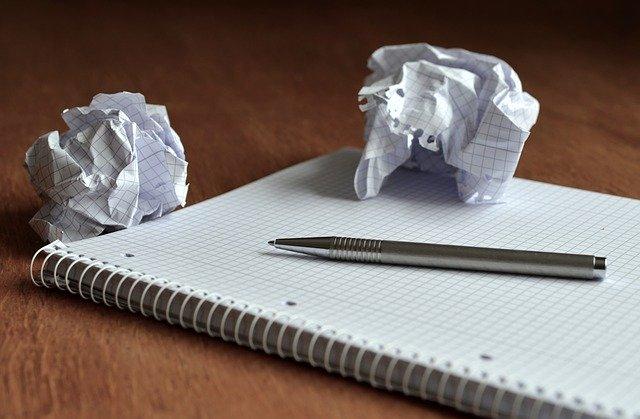 ノートの上にペンとクシャクシャに丸められた紙が転がっている様子